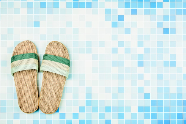 Sandals on blue ceramic tiles at the pool. - summer holiday concept background with copyspace Premium Photo