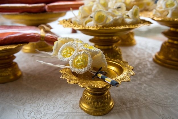 Sandalwood artificial flowers and yellow monk robe on golden tray for cremation Premium Photo