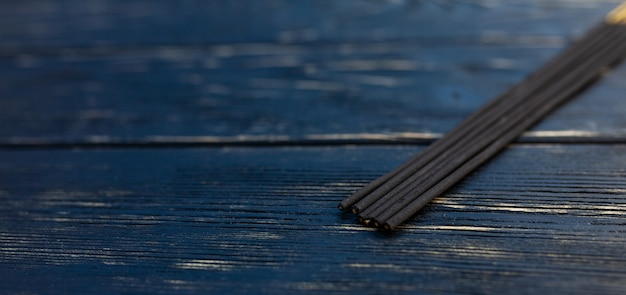Sandalwood sticks on a black wooden table. traditional asian culture. aromatherapy Premium Photo