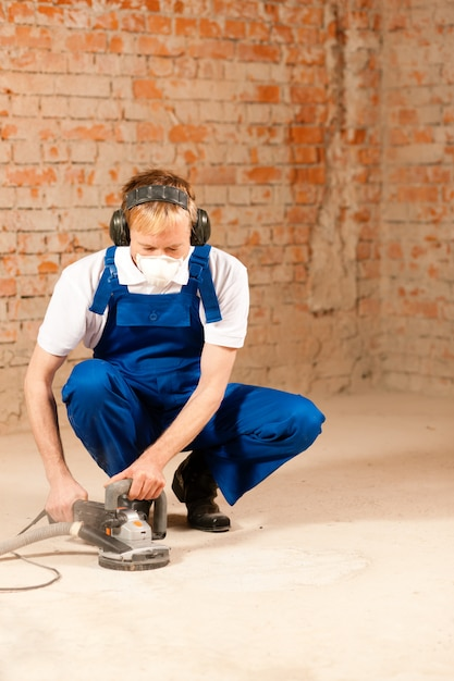 Sanding the cement floor Premium Photo