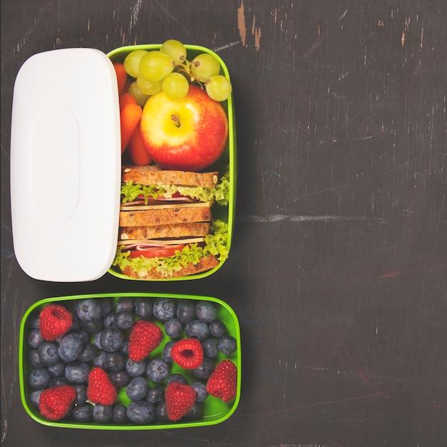 Sandwich, apple, grape, carrot, berry in plastic lunch box and b Premium Photo