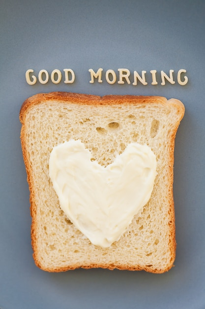 Sandwich for breakfast in the form of heart with cheese on a blue plate inscription good morning Premium Photo
