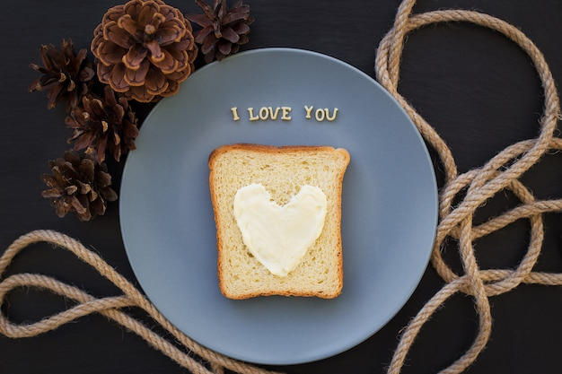 Sandwich for breakfast in form of heart with cheese on a blue plate Premium Photo
