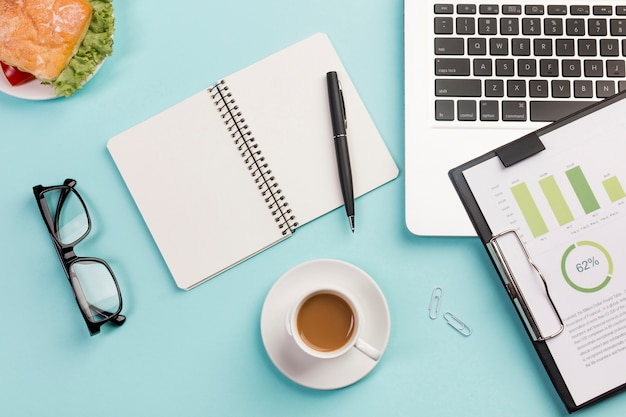 Sandwich,coffee cup,eyeglasses,spiral notepad,pen,laptop and clipboard with budget plan on blue desk Free Photo