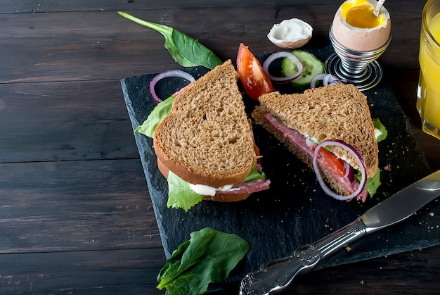 Sandwich, egg, cup coffe  and glass of juice for breakfast Premium Photo