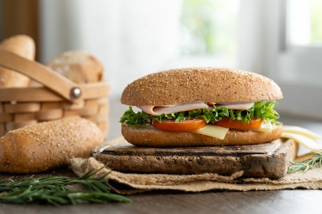 Sandwich ham and cheese with sesame bread and toasted bread on basket. Premium Photo
