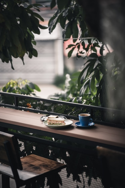 Sandwich and hot coffee on wood bar Premium Photo