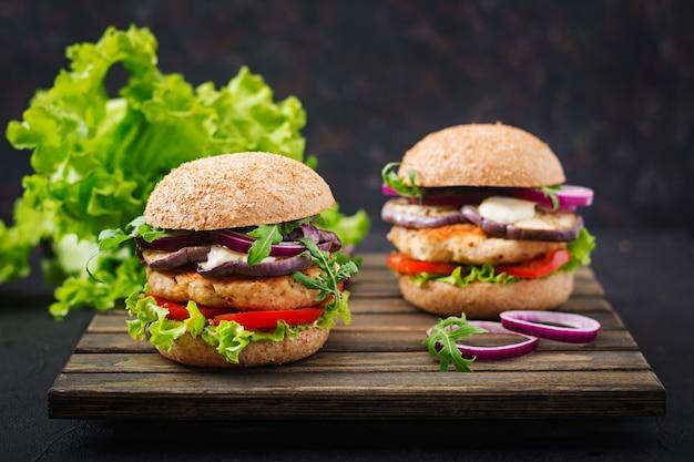 トマトとナスのジューシーなスパイシーチキンハンバーガーのサンドイッチ Premium写真