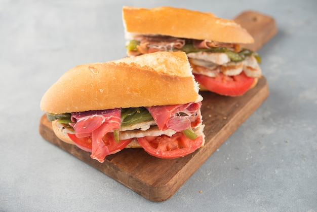 Sandwich serranito typical in andalusia with ham, gren pepper and grilled pork loin Premium Photo