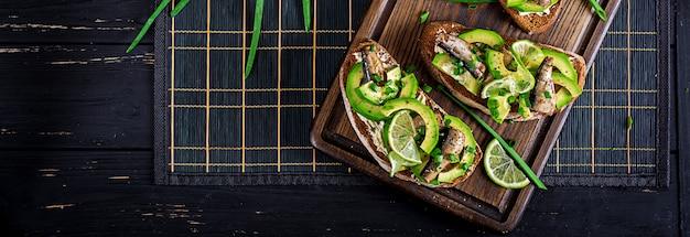 サンドイッチ-木の板にスプラッツ、アボカド、クリームチーズのスモレブロ。デンマーク料理。バナー。上面図 Premium写真