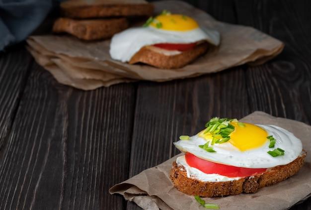 Panino su pane tostato con crema di formaggio, una fetta di pomodoro e un uovo fritto Foto Gratuite