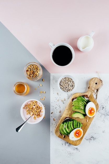 Sandwich with avocado and boiled eggs, yogurt with granola, cup of coffee over tricolor background Premium Photo