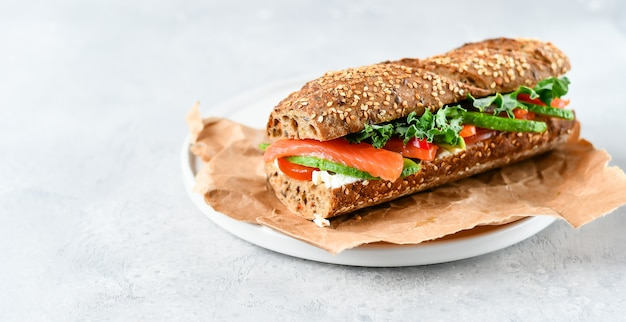 Sandwich  with avocado, salmon, cream cheese, tomatoes and lettuce leaves Premium Photo