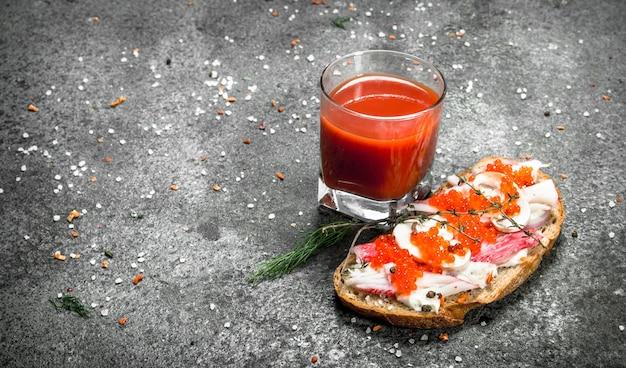 Бутерброд с крабовым мясом, красной икрой, овощами и стаканом томатного сока на деревенском столе. Premium Фотографии