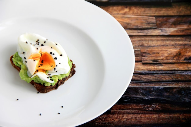 Sandwich with egg in a white plate on a wooden background Premium Photo