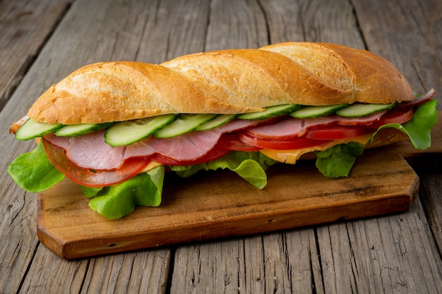 Sandwich with ham, cheese, tomatoes, cucumbers, lettuce on dark wooden background Premium Photo