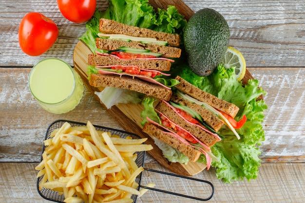 Бутерброд с лимоном, авокадо, картофелем фри, помидорами на деревянной доске и разделочной доской Бесплатные Фотографии