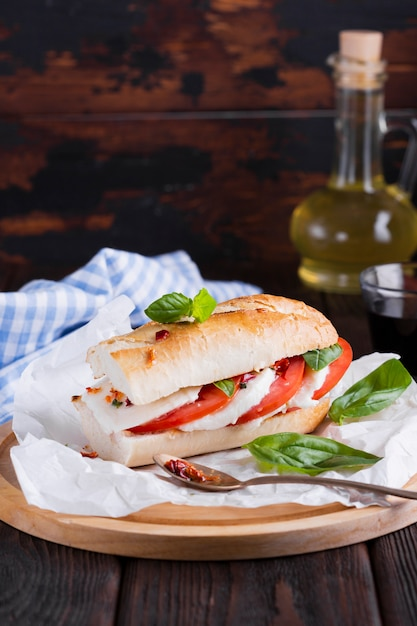Sandwich with mozzarella and basil on a table Free Photo