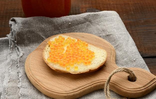Сэндвич с красной икрой лосося на деревянной доске Premium Фотографии