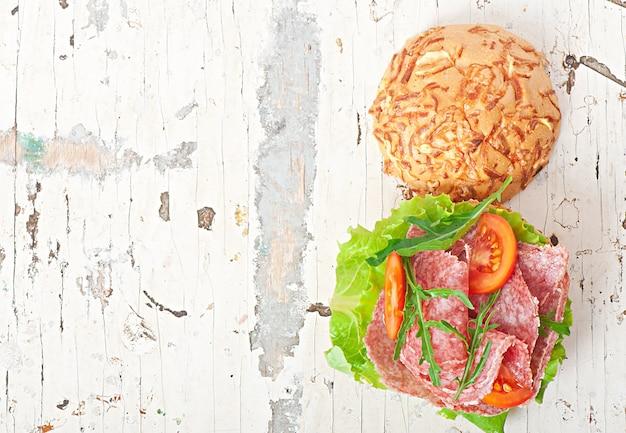 Sandwich with salami, lettuce, tomato and arugula Free Photo