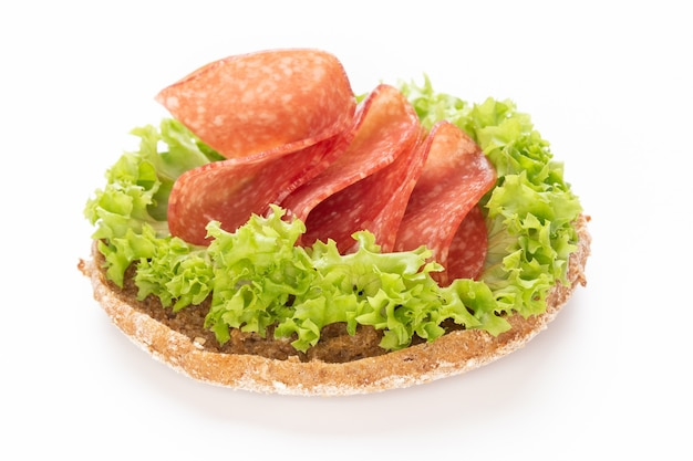 Sandwich with salami sausage on white surface. Premium Photo