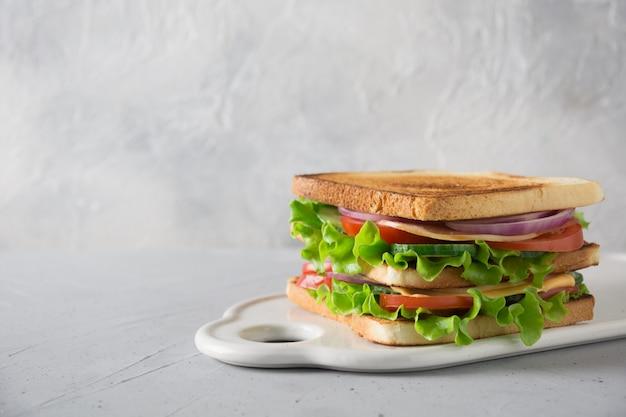 Sandwich with white toast bread, bacon, tomato, onion, salad, cheese on white. Premium Photo