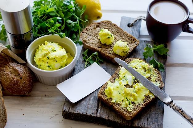 Бутерброды на завтрак с домашним маслом, приправленным пряностями, с цедрой лимона, куркумой, специями. ржаной хлеб Premium Фотографии