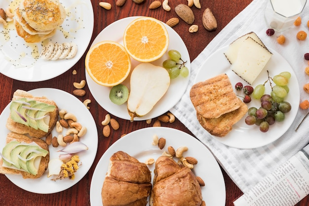 Sandwiches; fruits; dry fruits on plate over wooden table Free Photo