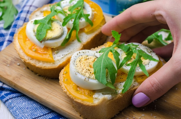 Sandwiches with boiled eggs, yellow tomatoes and arugula. Premium Photo