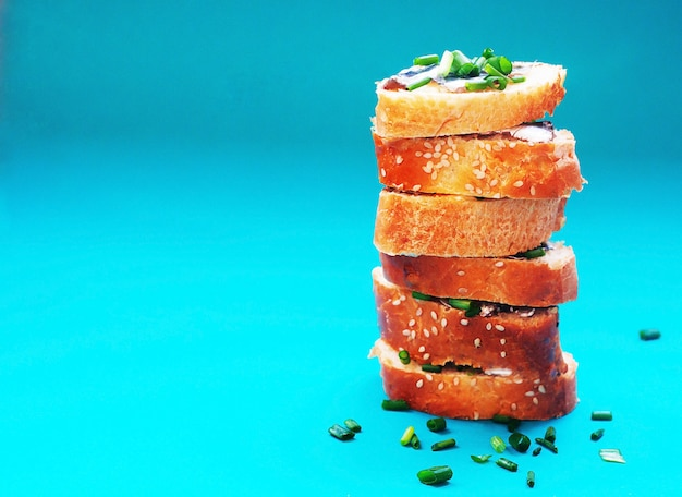 Sandwiches with butter and little salted fish for healthy snack on turquoise background Premium Photo