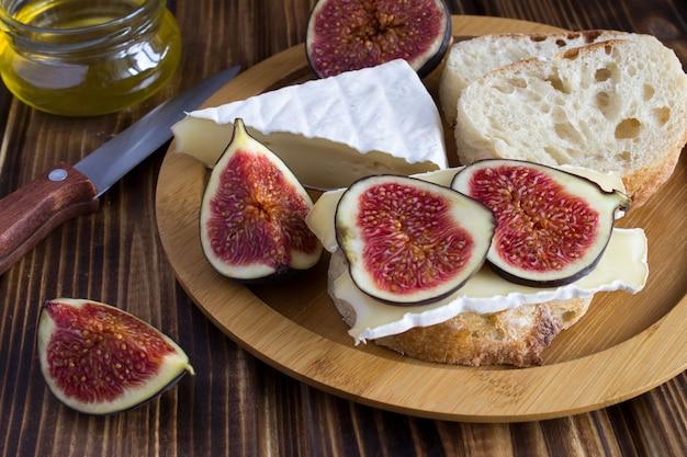Бутерброды с сыром и инжиром на коричневой разделочной доске Premium Фотографии