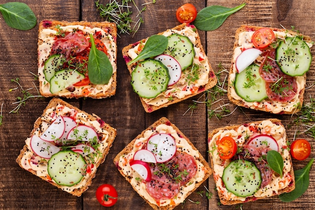 Sandwiches with cream cheese, vegetables and salami. sandwiches with cucumber, radish, tomatoes, salami on a gray surface, top view. flat lay. Premium Photo