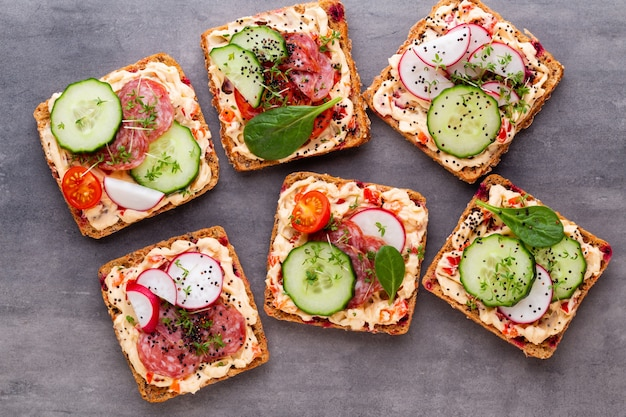 Sandwiches with cream cheese, vegetables and salami. Premium Photo