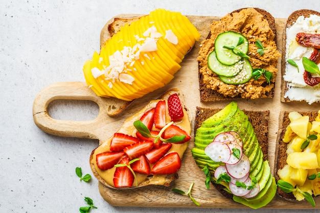 Sandwiches with mango, strawberry, tofu pate, avocado, potatoes and ricotta Premium Photo