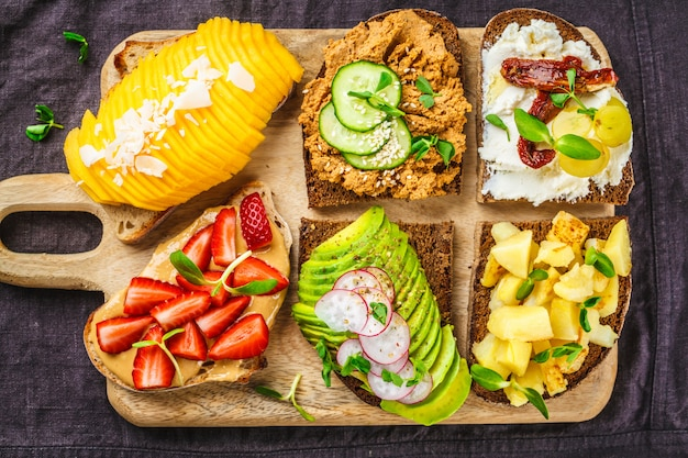 Sandwiches with mango, strawberry, tofu pate, avocado, potatoes Premium Photo