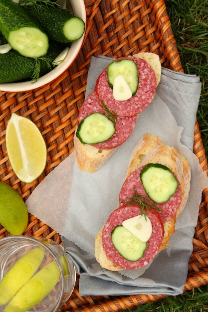 Sandwiches with smoked sausage and homemade fresh salted cucumbers in the bowl Premium Photo