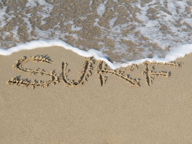 砂浜で波と砂で書かれた単語サーフ。 Premium写真