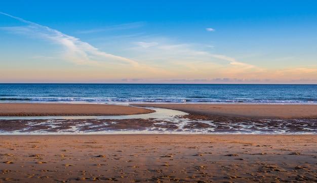 Песчаный берег моря с чистым небом Бесплатные Фотографии