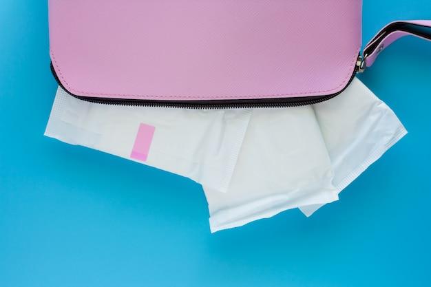 Sanitary napkin in women's pink bag on blue background Premium Photo