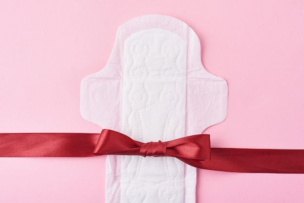 Sanitary pad and red ribbon on a pink surface Premium Photo