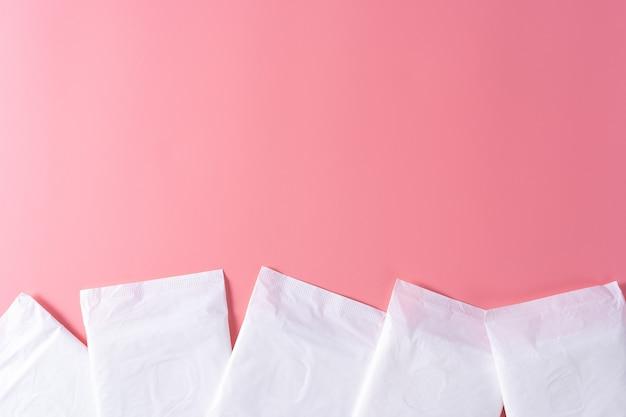 Sanitary pad, sanitary napkin on pink background. menstruation, feminine hygiene, top view. Premium Photo