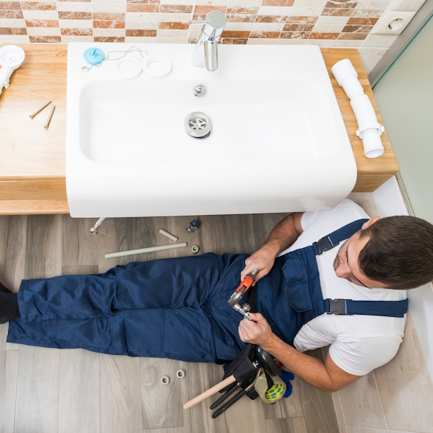 Sanitary technician working with sink Free Photo