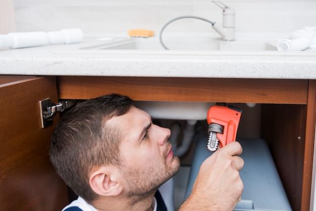 キッチンにレンチで働く衛生技術者 無料写真