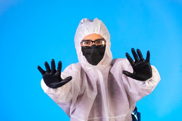特別な予防のユニフォームと黒いマスクの消毒剤は一時停止の標識になります。 無料写真