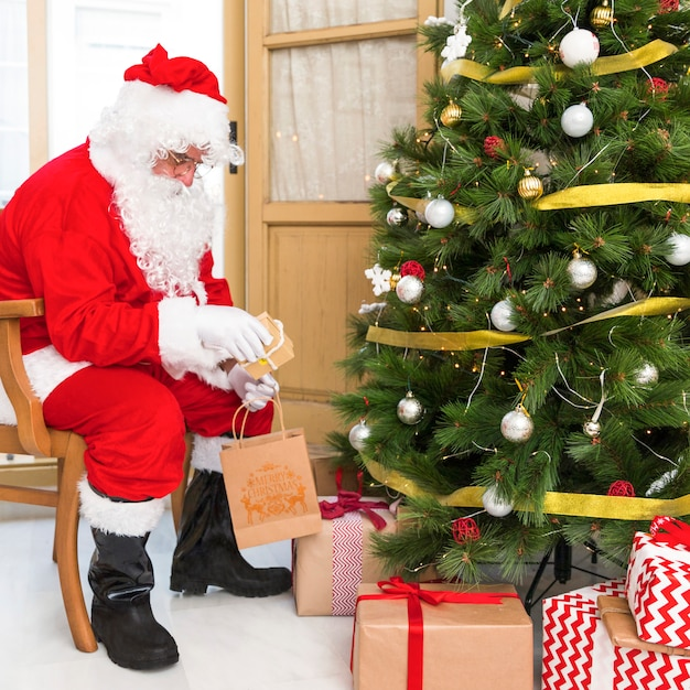 Santa claus on chair putting gifts under tree Free Photo