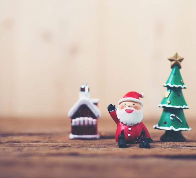 Santa claus character next to a christmas tree Free Photo