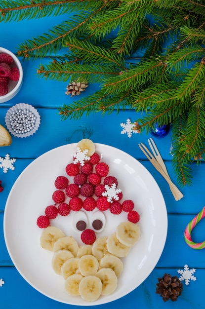 Santa claus face made of raspberries and banana with chocolate Premium Photo