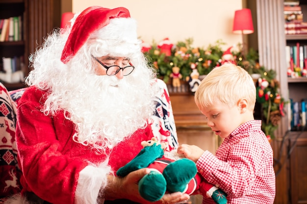 Santa claus giving a present to a kid Free Photo