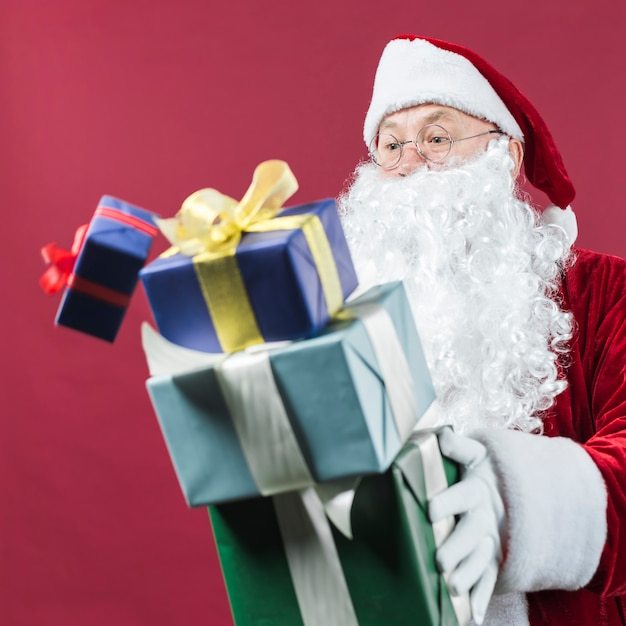 Santa claus in glasses dropping gift boxes Free Photo