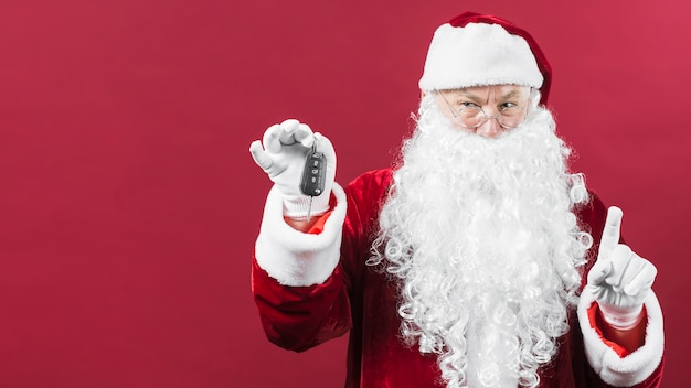 Santa claus in glasses holding car key in hand Free Photo